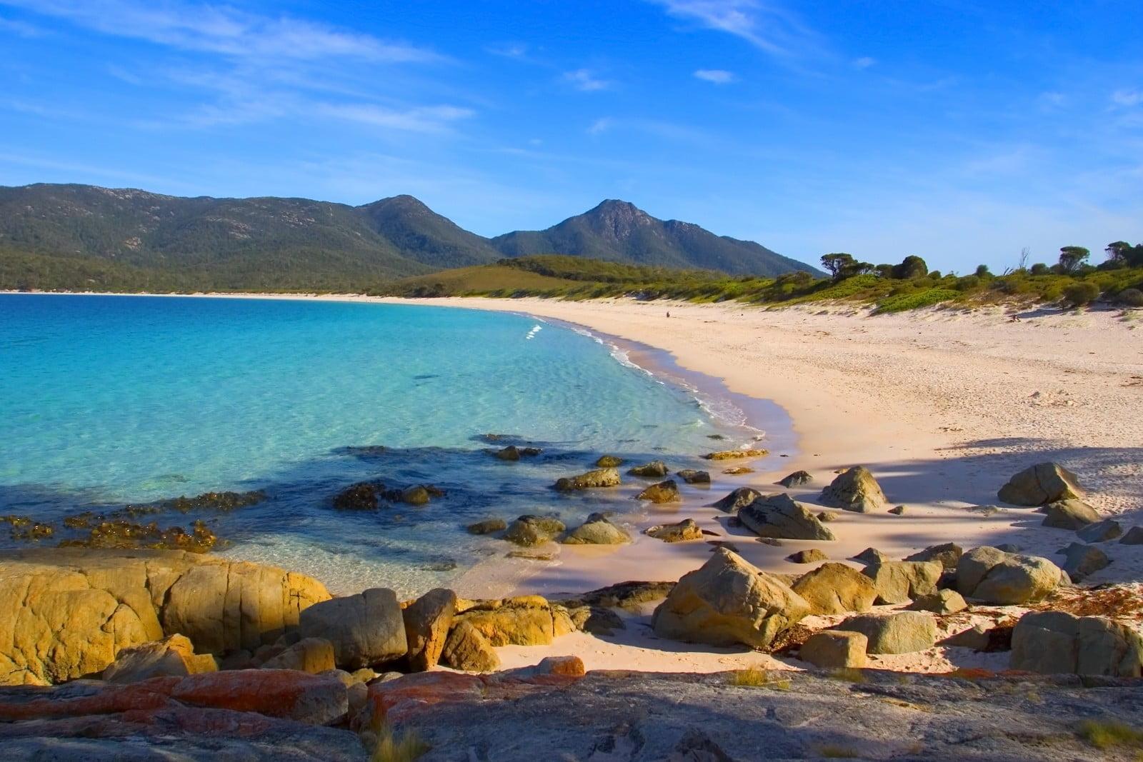 plage de sable avec des montagnes derrière