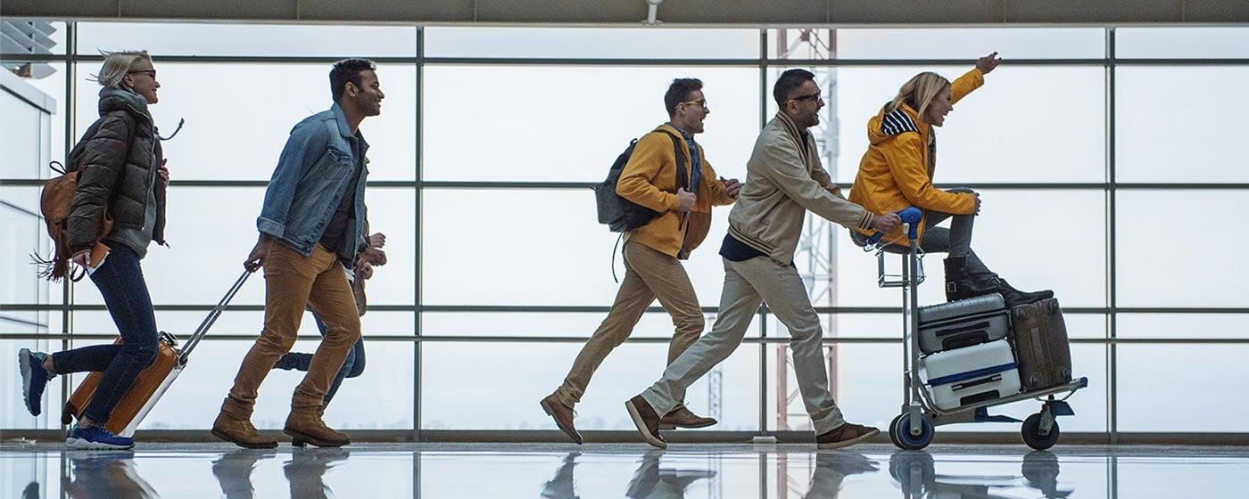 Groupe de voyageurs dans un aéroport qui poussent leurs valises