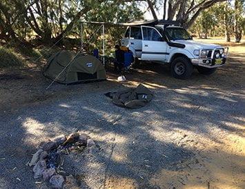 Campement avec une tente et un 4x4 lors d'un roadtrip